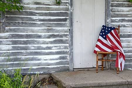 American Flag sitting outside a door to a wood house